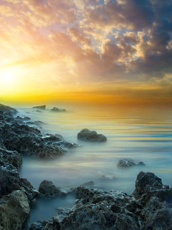 Marine sunset with a glow of the sun with stones and a calm sea water. Natural landscape