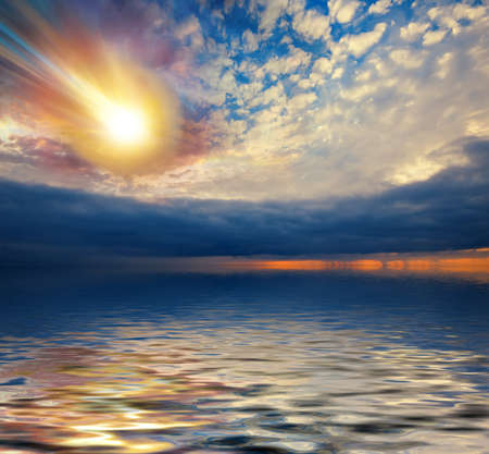 Huge fiery meteor falls into the sea on the background of dramatic clouds. invented composition Stock Photo
