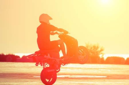 A man in a helmet on a moped shows stunts at sunset. Natural composition Stock Photo