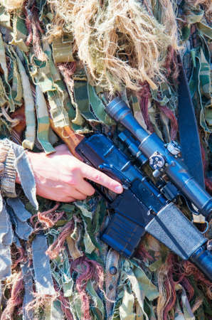 sniper training: A soldier in camouflage sniper holding a sniper rifle Vintorez. vertical composition Stock Photo