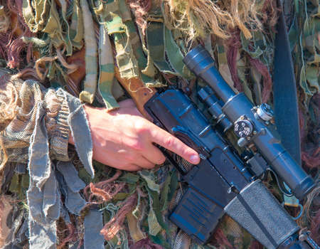 A soldier in camouflage sniper holding a sniper rifle Vintorez. Horizontal composition