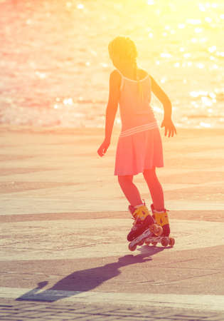 Girl roller-skating in the city center when it is backlit. Sport composition Stock Photo