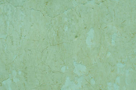 Peeling green plaster on the wall. textural composition