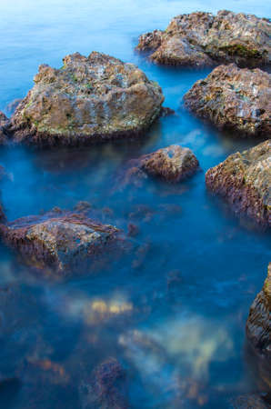 Sea and stones on a long exposure during sunset. Marine natural texture