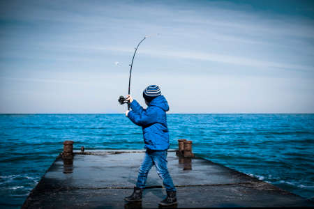 Little boy throws a fishing rod from the pier into the sea. Natural natural composition Stock Photo