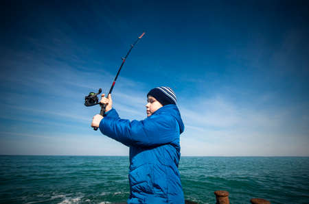 The little boy does cast a fishing rod in the sea. Natural natural composition