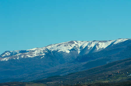Last snow in the mountains in early spring against a clean blue sky. Natural composition