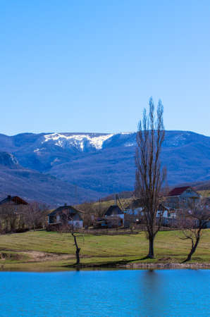 Lake in a mountain village against the backdrop of snowy mountains in early spring. Natural composition