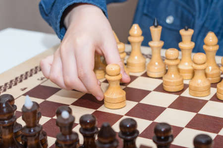 A little boy plays chess, makes the first move. Family composition