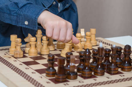 A little boy plays chess, makes his first move with a pawn. Family composition Zdjęcie Seryjne