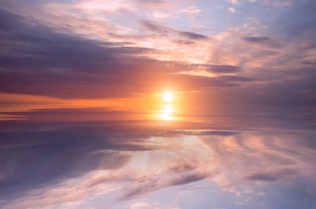 Sunset on the sky, bright sun and colorful clouds over the calm sea. Natural Dawn Composition Zdjęcie Seryjne