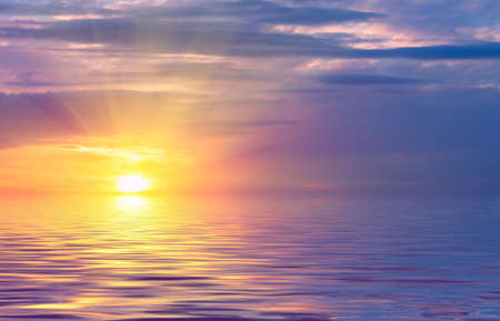 Sunset on the sky, bright sun and colored clouds over the rays against the backdrop of sea waves. Natural Dawn Composition