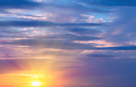 Sunset on the sky, bright sun and colorful clouds over the rays. Natural Dawn Composition