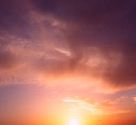 The bright orange sun rises against the backdrop of purple clouds. Natural sunset composition