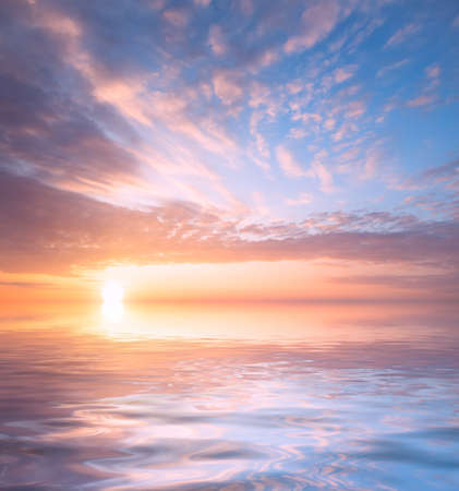 Beautiful sunset, bright sun and soft, multicolored clouds against the background of the sea. Natural dawn composition