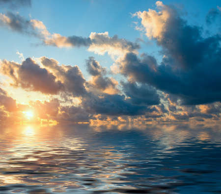 The bright rays of the sun in the dramatic clouds at dawn over sea. Natural sunset composition