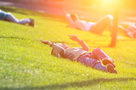 A little boy is lying on the green grass under the bright sun and having fun. Family composition Zdjęcie Seryjne