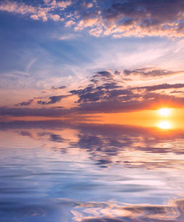 Heavenly sunset with the rays of the sun in the blue sky over the quiet, calm sea. Natural dawn composition.