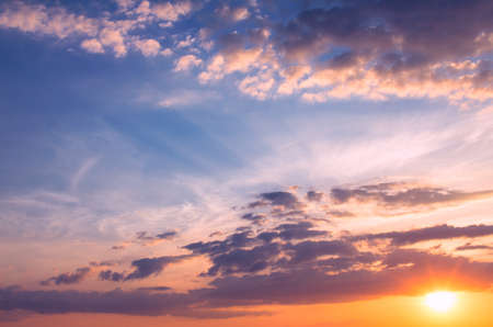 Heavenly sunset with sun rays in the blue sky. Natural dawn composition.