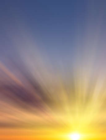 Beautiful sunrise with clouds of different colors and the rays of the sun against the blue sky. Abstract sunset composition