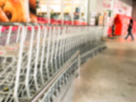 Blur image pushing a shopping cart in the supermarket.