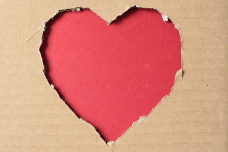 Grunge heart on ragged cardboard background photo