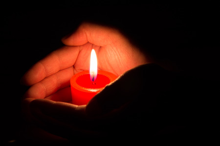 hands holding a burning candle photo