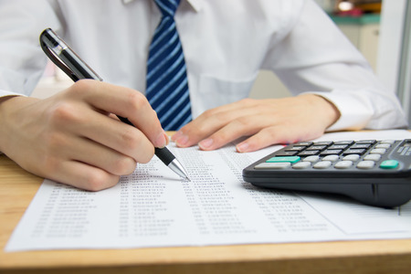 calculator chinese: Businessman calculating the financial statements Stock Photo