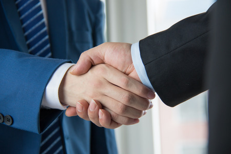 to the hand: business people handshaking