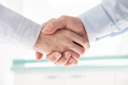 Arts en zakenman handen schudden Stockfoto