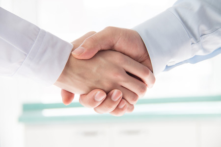 business partner: Doctor and businessman shaking hands