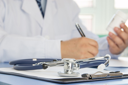 Close-up of stethoscope and folder on background of doctors at work Stock Photo