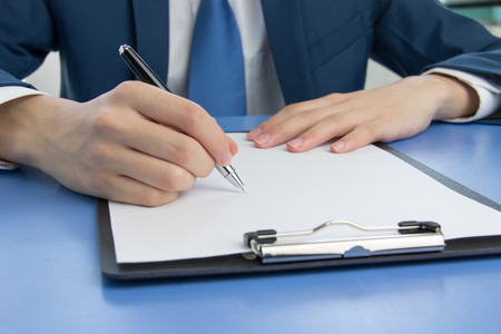businessman signing documents: Businessman signing documents in the office