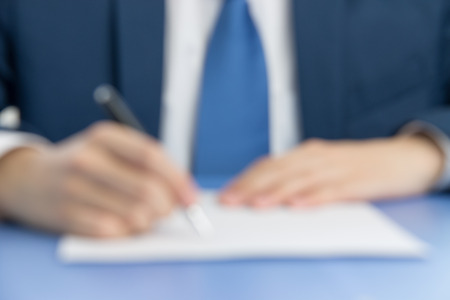 businessman signing documents: businessman signing documents to businessman in blur background