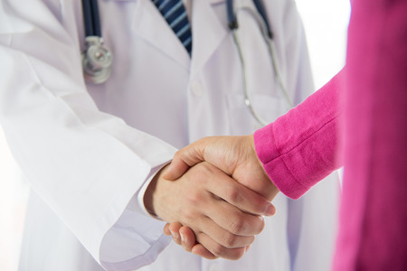 young male doctor: Doctor and patient shaking hands Stock Photo