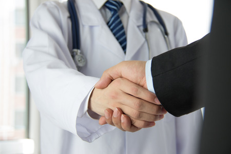 hand: Doctor and businessman shaking hands