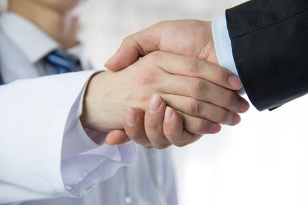 dando la mano: Doctor y hombre de negocios dándose la mano Foto de archivo