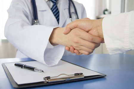 estetoscopio: Doctor y hombre de negocios d�ndose la mano Foto de archivo