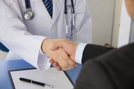 businessmen shaking hands: Doctor and businessman shaking hands