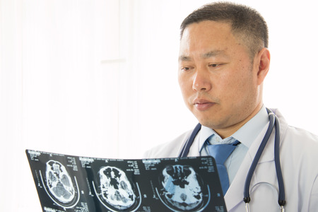 radiologist: Asian male doctors radiologist studying patients x-ray