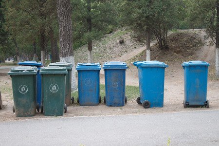 blue bin: green and blue garbage bin in the park
