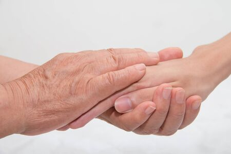 hand care: Elderly woman holding a young hand Stock Photo
