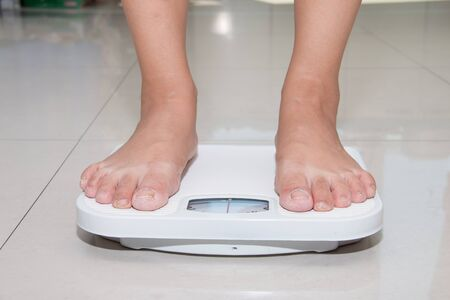 weighing scale: Closeup of a Asians weighed