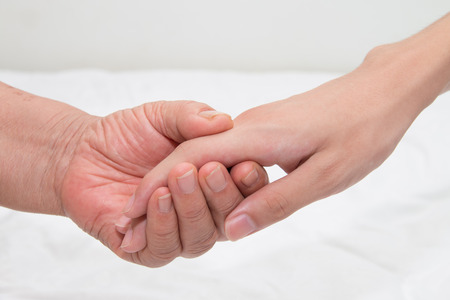 asian hospital: Elderly woman holding a young hand Stock Photo
