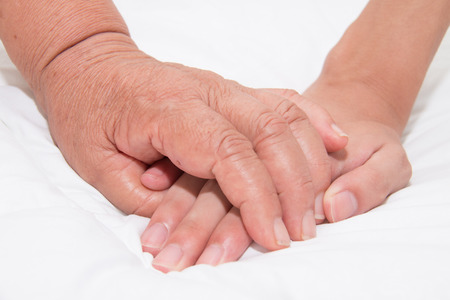 caring: Elderly woman holding a young hand Stock Photo