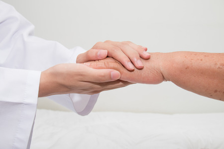 Doctor holding an old woman's hand Stock Photo - 43763048