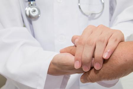 歳の女性の手を握って医師 写真素材