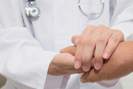 Doctor holding an old woman's hand Stock Photo - 43763052