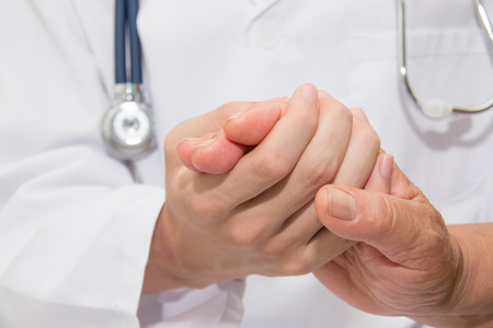 Doctor holding an old woman's hand