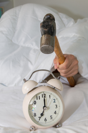 smashing: Closeup of a man with a hammer smashing alarm clock Stock Photo